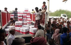 Yemenis drop off boxes of humanitarian aid provided by the Emirati Red Crescent in the coastal town of Mujailis, south of al-Hodeidah city, on June 6th. [Nabil Hassan/AFP]
