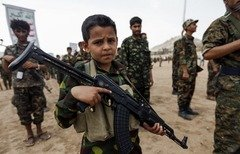 A Yemeni boy poses with a Kalashnikov assault rifle during a gathering of newly-recruited Houthi fighters in the capital Sanaa, to mobilise more fighters to the battlefront on July 16th, 2017. [Mohammed Huwais/AFP]