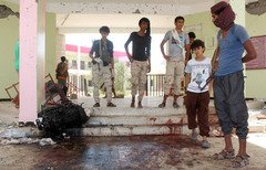 Yemenis look at a blood-stained floor at an army recruitment centre in Aden following a suicide car bombing claimed by ISIS in this file photo from August 29th. The attacker drove an explosives-laden vehicle into a gathering of army recruits at a school, killing at least 60. [Saleh al-Obeidi/AFP]