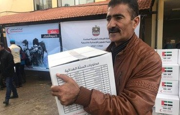 "A Syrian refugee receives a food aid package as part of the UAE Response Campaign for Displaced Syrians, ""Winter 2019"", launched in Lebanon in early January. [Photo courtesy of the UAE embassy in Lebanon]"