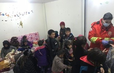 Basmeh and Zeitooneh workers distribute aid to Syrian refugee families at one of their centres in Lebanon. [Photo courtesy of Basmeh and Zeitooneh]