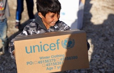 A Syrian refugee child in Lebanon receives a box of winter clothes from UNICEF. [Photo courtesy of UNICEF]